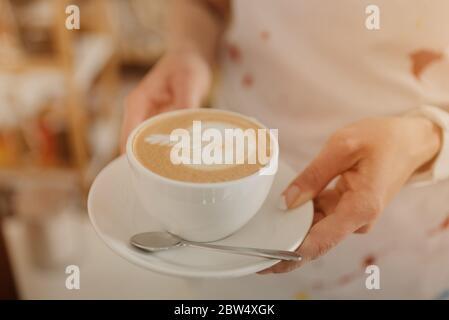 Ein Nahaufnahme-Foto eines Latte, den eine Barista in einem Café in den Händen hält. Ein Barista bereitet eine Bestellung in einem Café vor. - Stockfoto