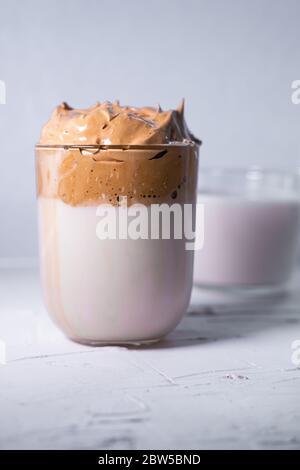 Dalgona Kaffee und Milch im Hintergrund. Koreanischer Eiskaffee. Vertikales Bild. - Stockfoto