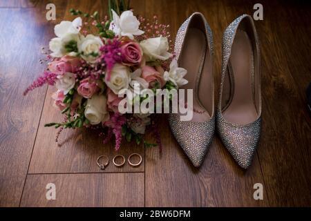 Eine Hochzeit goldene Ringe mit Braut Schuhe und Dekor - Stockfoto