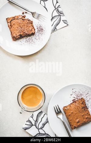 Blick von oben auf eine Tasse Kaffee und zwei Dessertteller mit Brownie-Kuchen auf weißem rustikalem Hintergrund. - Stockfoto