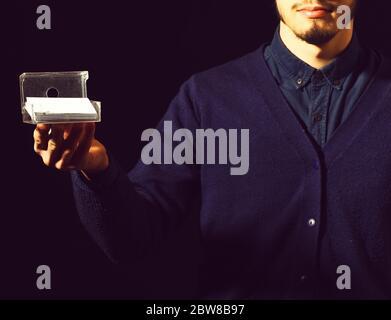 Männliche Hand des bärtigen Mannes in blauen Pullover Holding-Box für Visitenkarten in schwarzen Studio Hintergrund - Stockfoto