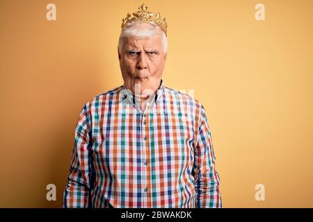 Senior schönen hoary Mann trägt goldene Krone des Königs über isolierten gelben Hintergrund machen Fisch Gesicht mit Lippen, verrückt und komische Geste. Witzige Ex - Stockfoto