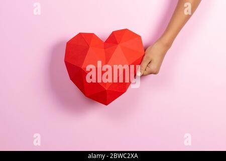 Hand hält rote polygonale Papier Herz Form auf hellrosa Hintergrund - Stockfoto