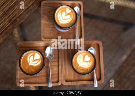 Zwei Tassen heißen Cappuccino auf dem Teller mit Löffeln auf weißem Holztisch Hintergrund. Platz für Text. Draufsicht. Stockfoto