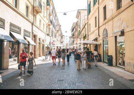 Italien, Verona, 01. Juni 2019: Einheimische und Touristen gehen oder gehen entlang einer Stadtstraße. Sie gehen Sightseeing oder gehen ihre täglichen Geschäfte. - Stockfoto