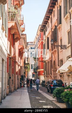 Italien, Verona, 01. Juni 2019: Traditionelle alte Straße. Einheimische und Touristen gehen oder gehen entlang einer Stadtstraße. Sie gehen Sightseeing oder gehen über ihren Schwanz - Stockfoto
