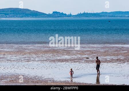 Longniddry Bents, East Lothian, Schottland, Großbritannien, 1. Juni 2020. UK Wetter: Heißer Sonnenschein am Strand bringt Leute raus, obwohl der öffentliche Parkplatz noch geschlossen ist. Die verschwommene markante Silhouette von Edinburgh liegt in der Ferne. Ein Mann und ein Kind am Strand - Stockfoto