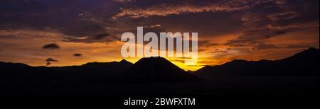 Atemberaubender dramatischer Sonnenuntergang hinter der Silhouette der Bergkette, die Mount Semeru, Mount Batok und Mount Bromo in Ostjava, Indonesien. - Stockfoto