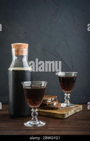 Traditionelles russisches Getränk Kvass aus Brot, Roggenmalz, Zucker und Wasser. Kvass in Flasche mit Roggenbrot und Glas auf schwarzem Hintergrund. - Stockfoto
