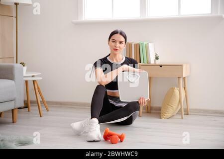 Junge Frau mit Messwaagen zu Hause - Stockfoto