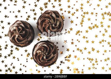 Drei köstliche Schokolade Cupcakes mit Schokolade Glasur und bestreut Gold funkelt auf weißem Hintergrund mit goldenen Stern Konfetti. Urlaubskonz - Stockfoto