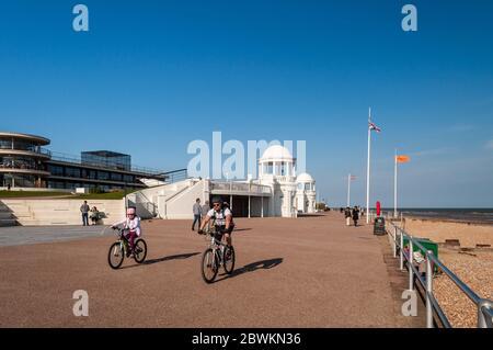 Bexhill on Sea, England, UK - 8. Juni 2013: Die Leute radeln und spazieren auf der Promenade vor dem Art-Deco-Pavillon De La Warr an der Strandpromenade von Bexhill - Stockfoto