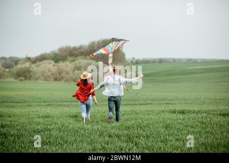 Glückliches Paar, das Spaß zusammen hat, mit Drachen auf dem Greenfield spielt. Glückliches Paar erwartet ein Baby und junge Familie Konzept Stockfoto