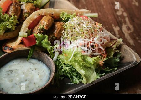 Falafel Pocket Pita. Mit Babaganoush, mit Krautsalat & Falafel serviert mit Beilage Salat & vegane Tzaziki.