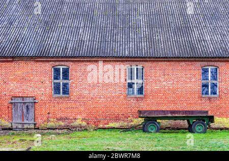 Landeidylle mit abgewracktem Anhänger vor einem baufälligen Ziegelstallgebäude, Mecklenburg-Pommern, Deutschland. - Stockfoto