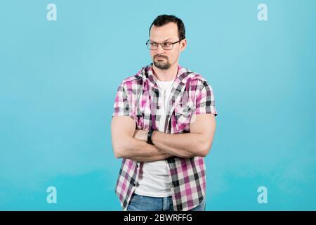 Ein junger Mann mit Bart in Brille und einem klerikalen Hemd faltete seine Arme über seine Brust und blickt mit einem Anspruch weg, wobei er eine Augenbraue hob - Stockfoto