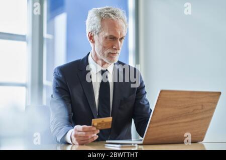 Geschäftsmann mit Kreditkarte und Laptop am Schreibtisch im Büro - Stockfoto