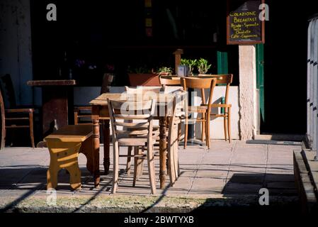 Leere Tische und Stühle im Café von Venedig, die die Auswirkungen der Wirtschaftskrise durch das Coronavirus zeigen - Stockfoto