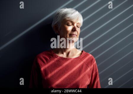 Porträt einer älteren Frau mit geschlossenen Augen, die sich an der Wand lehnt