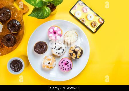 Bunte Donuts auf einem weißen Teller auf gelbem Hintergrund serviert. - Stockfoto
