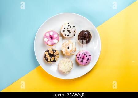 Bunte Donuts auf einem weißen Teller auf kreativem Hintergrund serviert. - Stockfoto