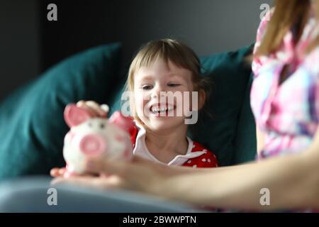 Kleines Mädchen lacht und legt Münze in Sparschwein - Stockfoto