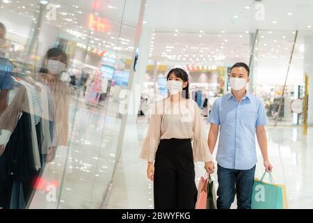 Asiatische Paar trägt Maske über ihr Gesicht suchen neue Kollektion Kleid im Einkaufszentrum mit Einkaufstasche für die Gesundheitsversorgung und Prävention von coronavir - Stockfoto