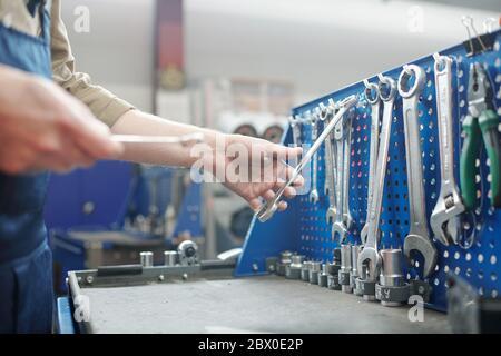Nahaufnahme eines nicht erkennbaren Reparaturwerkers, der in einer modernen Werkstatt ein Arbeitswerkzeug auf der Werkbank auswählt - Stockfoto