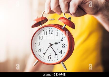 Ursache Zeit, Ruhezeit - EIN Mann hält einen Wecker und zeigt Zeit - Konzept - nicht Zeit umsonst verschwenden