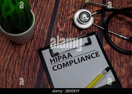 HIPAA Compliance Schreiben Sie auf Papierkram isoliert auf Holztisch.