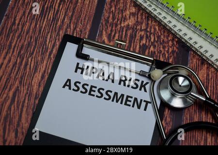 HIPAA Risikobewertung Schreiben Sie auf Papierkram isoliert auf Holztisch.