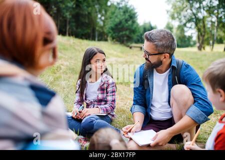 Gruppe von Schulkindern mit Lehrer auf Exkursion in der Natur, Lernen Wissenschaft. - Stockfoto