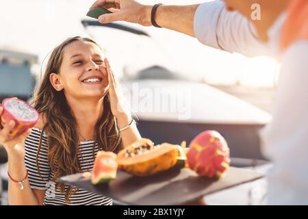 Glückliches Kind, das tropische Früchte isst, während es mit Vater - Vater und Tochter spielt, die am Wochenende sonnigen Tag zusammen Spaß haben