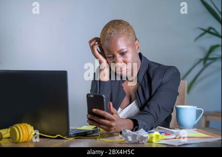 Junge verzweifelte und betonte afroamerikanische Geschäftsfrau, die am Laptop-Computerschreibtisch im Büro arbeitet und unter Stress leidet, das Problem mit dem Mobiltelefon Ove - Stockfoto