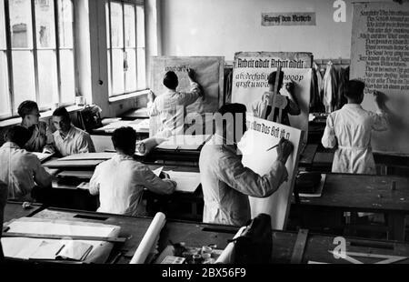Blick in ein Klassenzimmer einer Berliner Handwerkerschule, in der Schüler in Kittel üben, Slogans an Gebäudewänden zu schreiben. An der Wand steht der Slogan 'Kampf dem Verderb'. - Stockfoto