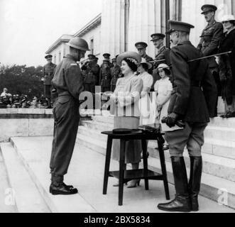 Königin Elizabeth ehrt A.H. Taylor als besten Kadett am Sandhurst College, indem sie ihm ein kleines silbernes Schwert übergibt. Im Hintergrund ihre Töchter Prinzessin Elizabeth und Prinzessin Margaret Rose. - Stockfoto