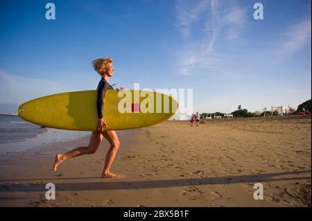Junge attraktive und glückliche blonde Surfer Mädchen in schönen Strand tragen gelbe Surfbrett aus dem Meer laufen genießen Sommerferien in Tropica - Stockfoto