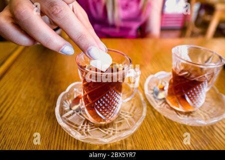 Die Hand der Frau, die in Petra, Jordanien, einem von zwei tot-Gläsern Tee zuschüttet. - Stockfoto