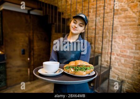 Nahaufnahme Porträt einer schönen kaukasischen Frau Kellnerin lächelnd fröhlich ein Tablett mit einer Tasse leckeren heißen Kaffee und frisch gebacken - Stockfoto