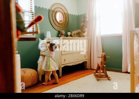 Mädchen umarmt ihr Stofftier in ihrem Zimmer