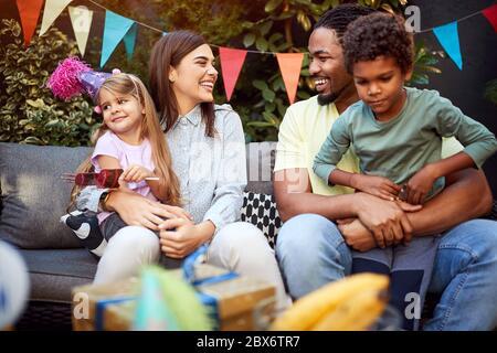 Fröhlicher Mann und Frau mit Kindern auf Geburtstagsfeier - Stockfoto