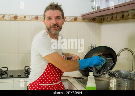 Home Lifestyle Porträt von glücklichen und attraktiven Mann in roten Schürze lächeln in der Küche Geschirr waschen und Pfanne fröhlich Hausarbeit und Domest - Stockfoto