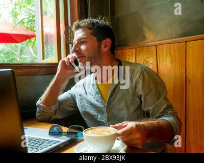 Junge attraktive glücklich und erfolgreiche Millennial Mann arbeitet aus Internet-Café mit Laptop-Computer im Gespräch auf Handy entspannt in entrepr - Stockfoto