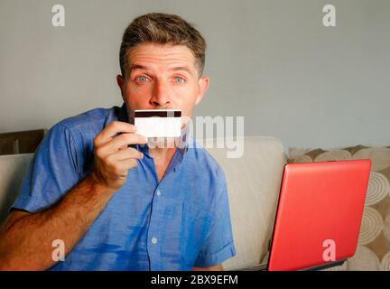 Junge attraktive und glückliche Mann entspannt zu Hause Sofa Couch mit Kreditkarte und Laptop-Computer für Internet-Shopping und Banking im Internet-Geschäft - Stockfoto