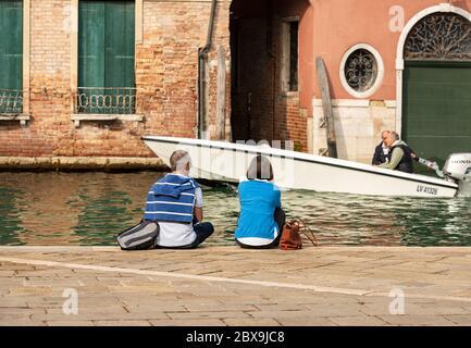 Ein paar Touristen sitzen am Rande eines Kanals, während ein Motorboot vor ihnen segelt. Venedig, UNESCO-Weltkulturerbe, Venetien, Italien, Europa - Stockfoto
