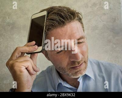 Grunge Porträt von frustriert und depressiv Geschäftsmann hält Handy in Stress Gefühl enttäuscht Leiden Kopfschmerzen und Angst suchen t - Stockfoto