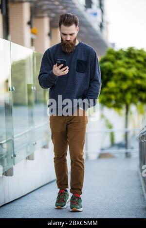 Schöner Mann mit Borsten im Freien. Mann mit lässigem Hemd halten Smartphone. Modernes Leben. Agiles Geschäft. Danke. Wie geht es Ihnen? - Stockfoto