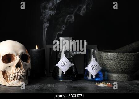 Tränke, menschlicher Schädel, Mörser und Stößel auf dem Tisch des Alchemisten Stockfoto