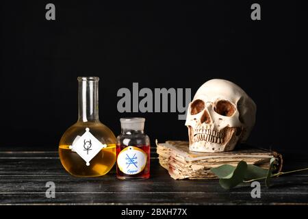 Tränke, menschlicher Schädel und altes Buch auf dem Tisch des Alchemisten Stockfoto