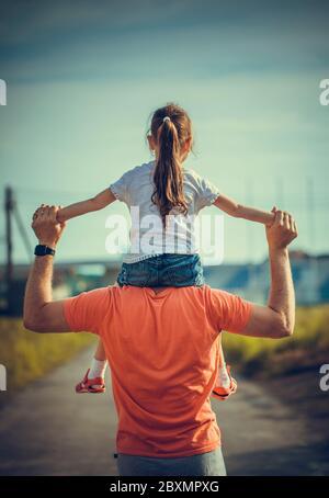 Papa tanzt auf seinen Schultern mit seiner Tochter in der Sonne. Vater reist mit Baby auf seinen Schultern in Strahlen des Sonnenuntergangs. Kind mit Eltern spaziert bei Sonnenuntergang - Stockfoto